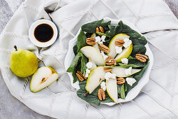 Served bowls with cut pears and pecan on table with pear walnuts