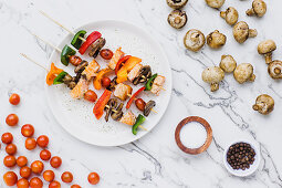 Pieces of cherry tomatoes sweet pepper salmon and mushrooms served on skewer on table with mushrooms