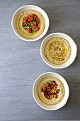 Three Bowls of hummus with various toppings