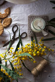 From above vintage scissors and linen thread placed on white fabric near yellow flowers and fresh desserts