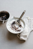 Whipped cream and melted chocolate being mixed