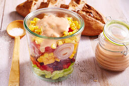 American layered salad with a yoghurt dressing in a glass
