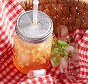 Apple and vanilla iced tea in a basket for a picnic