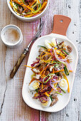 Panzanella with crispy vegetable strips, hard-boiled quail's eggs and sesame seeds