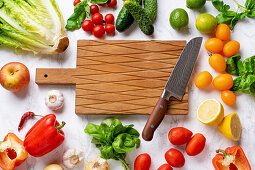 Fresh vegetables, salad leaves and greens, cutting board with chefs knife