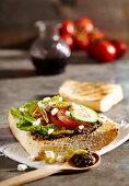 Grilled flatbread with tapenade, feta, tomato, cucumber, hot peppers and romaine lettuce