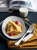 Baby banana stuffed crepes in caramel sauce with raspberries