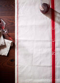 Laid table with a tea towel, red wine and a cloth napkin