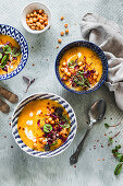 Creamy carrot parsnip soup with sorrel, chickpeas and microgreens served in blue bowls on gray background