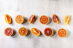 Group of fresh organic Sicilian blood oranges sliced and whole in row over white wooden background