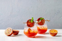 Blood orange iced cocktails in glasses, decorated by slice of oranges and fresh mint on skewers