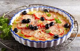 Potato pizza with tomatoes, mozzarella, oregano, basil and olives in a baking dish