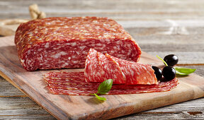 Sliced Italian salami spianata romana on a wooden board