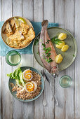 Baked lavaret fillets with porcini mushrooms, trout au bleu, and char and vegetables rolls