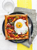 Small paprika puff pastry tart with fried egg