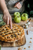 Person cuts freshly baked apple pie with cinnamon