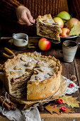 High autumn apple pie, in the background a person in a sweater holds a piece of cake
