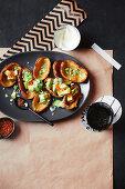 Potato skins with avocado and smoked salmon pearls
