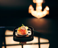 A salmon canapé on a serving platter on a dark surface