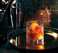 An Old Fashioned cocktail on a tray