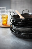 A stack of paella pans