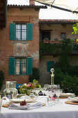 A festively laid table with wine and water carafes in front of a brick facade