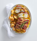 Marinated monkfish wrapped in bacon in saffron sauce with potatoes