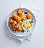 Potato and salmon balls with turmeric-yoghurt sauce