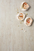 Guava-rippled meringues topped with pistachios