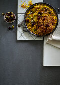 Saffron and sultana millet with spicy baked cauliflower and marinated olives