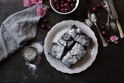 Chocolate cake with cherries and icing sugar