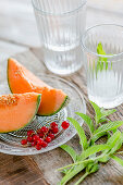 Melon wedges and redcurrants on a glass plate next to glasses and mint