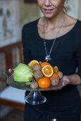 A woman holding a platter of fruit