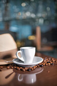 Ceramic cup with teaspoon on round saucer among roasted coffee beans beside hat with brim and empty mug dropped on wooden table