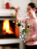 Christmas decorations hanging from cord in front of fireplace