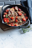 Beef steaks with an anchovy sauce, oregano and braised tomatoes