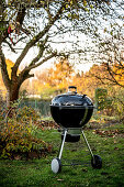 A kettle grill in an autumnal meadow by a lake