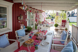 Set table on festively decorated terrace outside Falu-red wooden house