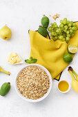 Zutaten für gesundes Frühstück: Haferflocken, Trauben, Guave, Limetten, Bananen und Birnen