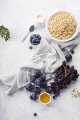 Zutaten für gesundes Frühstück: Haferflocken, Pflaumen und Trauben