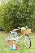 Bicycle and vintage picnic suitcase on a summer meadow