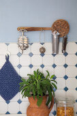 Perforated wooden spoon used as wall bracket for kitchen utensils