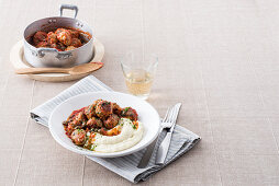 Meatballs in tomato sauce with capers on mashed potatoes