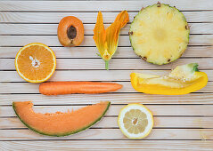 Flatlay of orange and yellow fruits and vegetables arranged on a wooden background