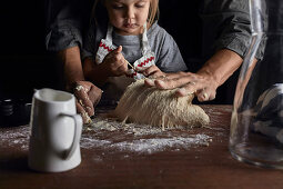 Father and daughter kneading the dough together