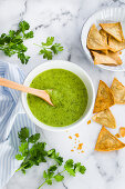A bowl containing fake guacamole sauce made with zucchini, cilantro and green chillies (not avocado at all).