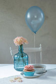 Balloon floating over table set in pale blue and pink
