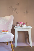 Stool, armchair and romantic accessories against brown wall