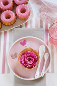 Pink ranunculus in muffin case on plate as table decoration