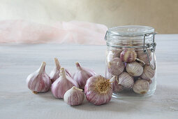 Fresh garlic bulbs in and next to swing-top jar